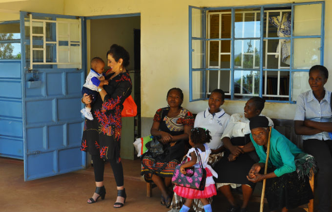 Honorary Ambassador Ms. Gina Din greets a mother and her baby at the Uhiri Health facility during her visit